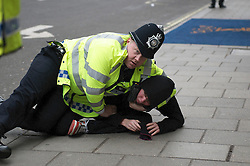 © under license to London News Pictures. 26/03/201.  A policeman pins down a protester in front of The Ritz Hotel in central London. PicturesHundreds of thousands of people take to the streets of London to protest against the Coalition Government cuts. Organised by the TUC the 'March for the Alternative' is the largest in London since the anti Iraq war protests. Photo credit should readMichael Graae/LNP.