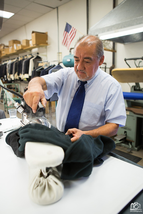 Tailor Luis Villafuerte irons a jacket after adjusting the seam stitching at Men's Wearhouse in Milpitas, Calif., on Sept. 19, 2012.  Photo by Stan Olszewski/SOSKIphoto.