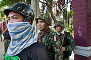 14 MAY 2010 - BANGKOK, THAILAND: Red Shirt protesters in front of Thai soldiers on a patrol at the intersection of Rama IV and Witthayu Roads in Bangkok Friday morning. Tensions among Red Shirt protesters demanding the dissolution of the current Thai government rose overnight after Seh Daeng, the Red Shirt's unofficial military leader was shot in the head by a sniper. Gangs of Red Shirts have taken over military checkpoints on Rama IV and are firing small rockets at military helicopters and army patrols in the area. Troops have responded by firing towards posters.  PHOTO BY JACK KURTZ