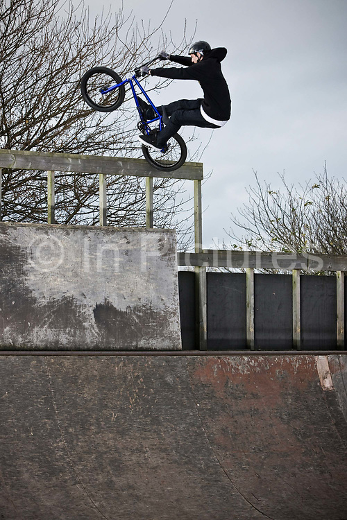 A professional BMX athlete doing a tail stall manoeuvre at a wooden skate park on the 25th November 2012 in Benfleet in the United Kingdom.