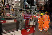 Two passing construction workers look towards the scaled printed version of a human colleague figure who warns pedestrians to stay on established footpath, and not wander into construction site roadways during street improvements in Victoria, central London. The project kown as VT12 is a multi-million Pound series of infrastructure improvements by Westminster city council in and around Victoria station.