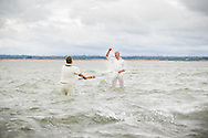 The first two players make their way onto the 'pitch' while the tide slowly recedes for the annual Bramble Bank cricket match in the middle of the sea. The eccentric game involves members of the Royal Southern Yacht Club in Hamble playing against the Island Sailing Club from Cowes on the Brambles, a patch of sand in the Solent, only visible for a few minutes on the spring tide. The teams take turns in winning. This year the Royal Southern team won and hosted dinner at their club house.<br /> Picture date Monday 31st August, 2015.<br /> Picture by Christopher Ison. Contact +447544 044177 chris@christopherison.com