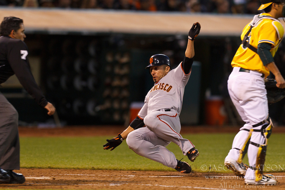 June 18, 2011; Oakland, CA, USA;  San Francisco Giants center fielder Andres Torres (56) slides into home to score a run past Oakland Athletics catcher Kurt Suzuki (8) during the fifth inning at the O.co Coliseum.