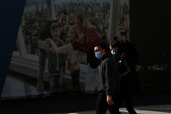 Couple with face mask near the World Tarde Center during the Covid-19 pandemic in New York City, NY, USA on April 22, 2020. The Big Apple neared a painful milestone Wednesday as the death toll from the coronavirus outbreak that has ravaged the five boroughs approached 15,000. The pandemic has claimed the lives of 14,996 New Yorkers, with new 569 fatalities reported in the most recent 24-hour period, according to data from the city's Department of Health. Photo by Charles Guerin/ABACAPRESS.COM