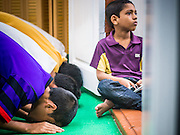 13 JULY 2013 - BANGKOK, THAILAND:  A boy sits in the doorway while men pray at Haroon Mosque during Ramadan. Ramadan is the ninth month of the Islamic calendar, and the month in which Muslims believe the Quran was revealed. The month is spent by Muslims fasting during the daylight hours from dawn to sunset. Fasting during the month of Ramadan is one of the Five Pillars of Islam. Muslims believe that the Quran was sent down during this month, thus being prepared for gradual revelation by Jibraeel (Gabriel) to the prophet Muhammad.        PHOTO BY JACK KURTZ