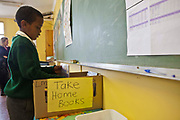 A young African school boy looks through the box of books to choose which one to take home by the green board in his classroom in Lourier Primary School, Cape Town, South Africa.  The books have been donated to the school by Life Matters Literacy Centre which aims to address the high illiteracy rates in South Africa by improving literacy levels among children in schools and disadvantaged communities.