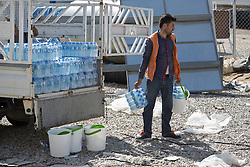 Licensed to London News Pictures. 20/10/2016. An aid worker prepares water packages to be handed, with food and basic hygiene kits, to Iraqi refugees who have recently arrived from areas liberated from the Islamic State in Iraq during the ongoing Mosul Offensive.<br /> <br /> The crowded Dibaga camp, housing around 28,000 Sunni Arab refugees, is the main gathering point for new IDPs now fleeing areas where ISIS have been pushed out or are in conflict with the Iraqi Army. Photo credit: Matt Cetti-Roberts/LNP