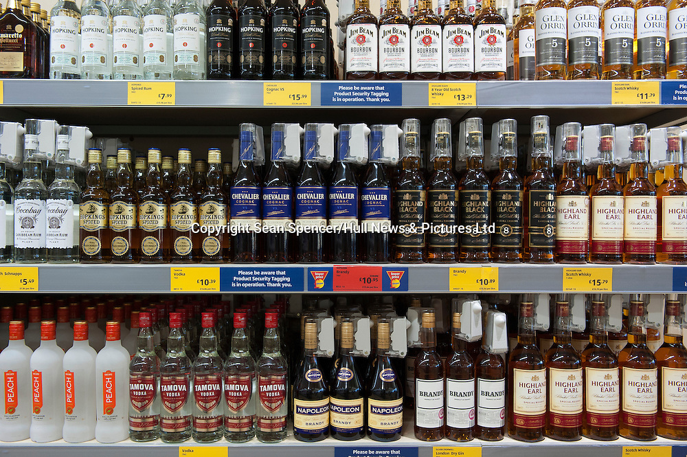 Bottles of cheap alcohol including brandy, whisky and vodka on shelves in a UK budget supermarket.