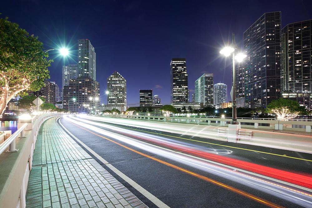 Streaking lights on Brickell key Drive with Brickell district skyline, Miami, Florida, USA