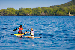 Young girls paddling out on standup paddleboard (SUB) to Captain James Cook Monument in Kealakekua Bay, Big Island, Hawaii, Pacific Ocean.