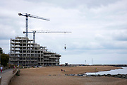 Construction cranes working on Folkestone seafront development on the 15th of July 2021, in Folkestone, United Kingdom. The development consisting of 84 homes is right on the beachfront towards the western end of the beach close to the Lower Leas coastal path and the Leas lift.
