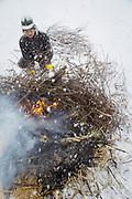 Man burning branches during winter, Nozawaonsen, Japan