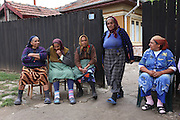 Old women congregate on a Sunday morning on the village streets. A Roma village. Piteasca village on the outskirts of Bucharest..Roma Gypsies left India 1000 years ago. Often nomadic. A collection of tribes with their own languages and culture, pushed by the Ottoman empire towards Europe, used and sold as mercenaries, slaves, prostitutes. They endured 500 years of slavery until mid 19th century. A million were killed in the holocaust. Hundreds of thousands exiled and refugees from kosovo. Many Eastern Europe Roma come to the west seeking a better life. They are shunned, marginalized, excluded. Both indigenous and foriegn Roma, whether European citizens or not, lack the opportunities of others, living on the periphery, in the brunt of racism, often deported back to their countries of origin.