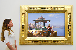 "© Licensed to London News Pictures. 11/10/2019. LONDON, UK. A staff member views ""The Harem in the Kiosk"", by Jean-Léon Gérôme, (Est GBP3-5m).  Preview of works from the Najd Collection of orientalist paintings at Sotheby's in New Bond Street, which record daily life in the historic Arab, Ottoman and Islamic worlds  All 155 paintings are on public view 11- 15 October, with 40 works to be auctioned on 22 October.  Photo credit: Stephen Chung/LNP"