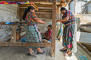 The long strings of thread are then loaded onto the main pedal weaver which is a large wooden structure with two pedals which help change the direction of weaving.  Four women are needed for this process.  Each individual string is tied by hand to a previously made loom, this takes two women two days work.