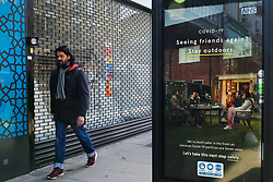 © Licensed to London News Pictures. 29/03/2021. London, UK. A man walks past the government's 'Seeing friends again? Stay outdoors.' latest advertising campaign poster in north London as lockdown restrictions across the UK are easing this week. The adverts remind the public that they must stay outside when meeting others. Photo credit: Dinendra Haria/LNP