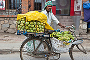 A Nepalese man pushes his bicycle loaded with fruit through the streets of Kathmandu, Nepal.  He sells fruit for a living on the street.