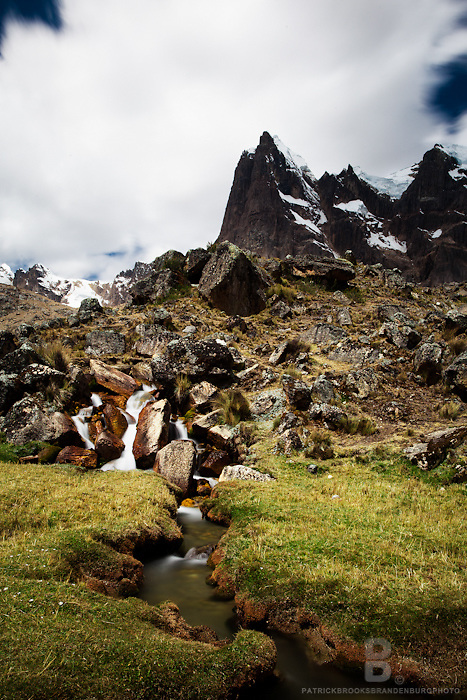 A long exposure looking at just the jagged part of Mt Cuyoc and a green pasture and stream in the Cordillera Huayhuash of the Andes Mountains in Peru.