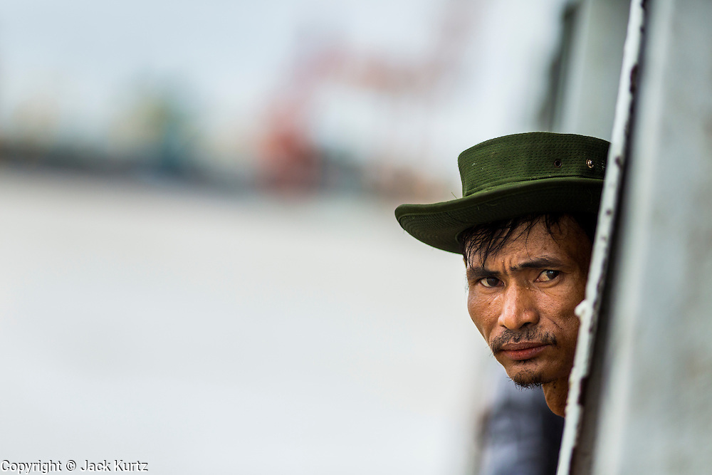 08 JUNE 2014 - YANGON, MYANMAR: A man leans out over the Yangon River on the ferry to Dala. The ferry to Dala runs continuously through the day between Yangon and Dala. Yangon, Myanmar (Rangoon, Burma). Yangon, with a population of over five million, continues to be the country's largest city and the most important commercial center.      PHOTO BY JACK KURTZ