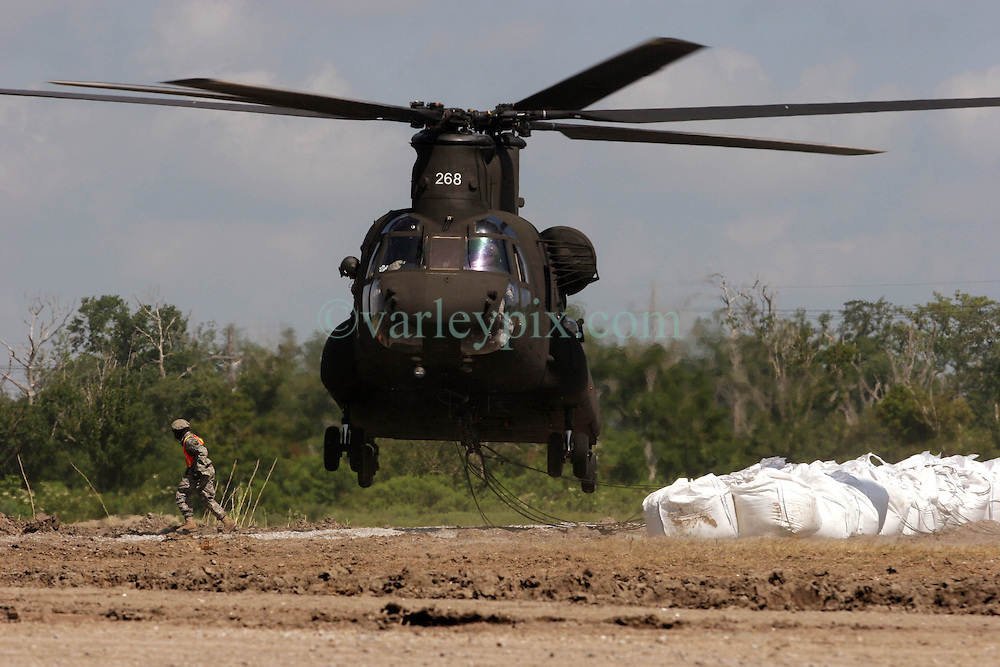 12 june 2010. Wetlands of Plaquemines Parish, South Louisiana. <br /> An army chinook CH-47 twin rotor helicopter on a sandbagging mission. Sand bags attempt to join the dots and connect what little remains of fragile barrier islands. It is unlikely the bags will survive a hurricane. Where once there was land, there is only the mere outline of old canals and channels, many dug by oil companies to pump their product ashore with little regard to the effects the chopping up of the wetlands would have. Chronic erosion of the land, a football pitch every 50 minutes, greatly reduced protection from hurricanes and impending BP oil slicks is the direct result of mismanagement and utter disregard for the environment. The army corps of engineers and the oil companies, together with inept government have a great deal to answer for. <br /> View from a blackhawk helicopter flown by airmen of the Nebraska Air National Guard over southern Louisiana as they assist in the dumping of sand bags onto barrier islands in a vain attempt to prevent BP oil from getting into the inner  wetlands. As valiant as their efforts are, the dumping of sand bags may well prove to be a complete waste of manpower, resources and money. A hurricane will likely roll over and blast through any sandbag 'barrier island,' blowing thousands of large white plastic bags far and wide across the landscape. That will really help the environment! <br /> Meanwhile, the mighty Mississippi river runs straight out to sea nearby, her valuable land building sediment carried far out into deep ocean as the region struggles to find a way to reverse the disastrous effects of man's interference with her flow. <br /> Photo credit; Charlie Varley/varleypix.com