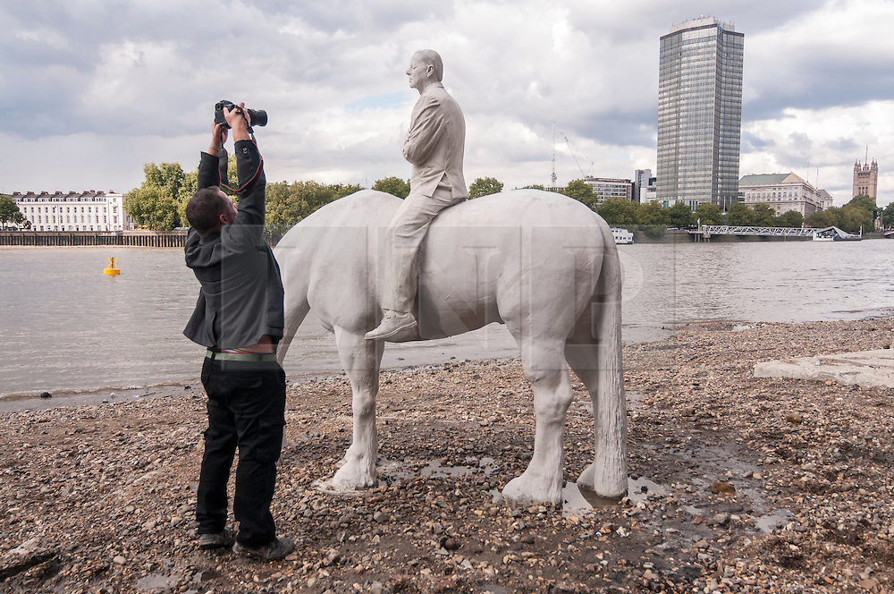 """© Licensed to London News Pictures. 02/09/2015 London, UK. The art installation entitled """"The Rising Tide"""" (comprising four horse-riders on horses with petroleum pumps for heads) by the underwater eco-sculptor Jason deCaires Taylor (pictured taking a photo), which stands on the foreshore of the River Thames in Vauxhall and is revealed with each low tide.  The installation aims to question man's reliance on fossil fuels and is part of this year's Totally Thames festival. Photo credit : Stephen Chung/LNP"""