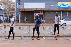 JOHANNESBURG, SOUTH AFRICA - APRIL 18: Social distancing while queing for groceries, during a South African Police Service (SAPS) Metro Police and Army supported patrol in Rockey Street, Yeoville. Random searchs and social distancing measures on April 18, 2020 in Johannesburg South Africa. Under pressure from a global pandemic. President Ramaphosa declared a 21 day national lockdown extended by another two weeks, mobilising goverment structures accross the nation to combat the rapidly spreading COVID-19 virus - the lockdown requires businesses to close and the public to stay at home during this period, unless part of approved essential services. (Photo by Dino Lloyd)
