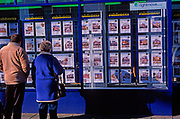 A728M3 Man and woman couple look in estate agent window at properties for sale