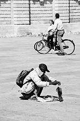 Lecce - Piazza Duomo - Un extracomunitario ordina la propria merce prima di venderla ai turisti. Sullo sondo alcune persone aprofittano della bella mattinata per girare il centro storico in bicicletta.