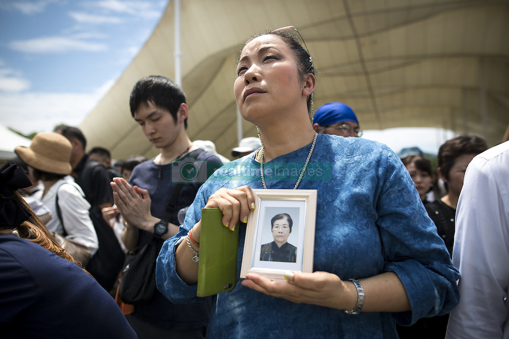 August 9, 2016 - Nagasaki, Nagasaki Prefecture, Japan - NAGASAKI, JAPAN - AUGUST 9 : A woman holding a photograph pray for the atomic bomb victims in front of the Peace Statue in Nagasaki Peace Park, Nagasaki, southern Japan, Tuesday, August 9, 2016. Japan marked the 71st anniversary of the atomic bombing on Nagasaki. On August 9, 1945, during World War II, the United States dropped the second Atomic bomb on Nagasaki city, killing an estimated 40,000 people which ended World War II. (Credit Image: © Richard Atrero De Guzman/NurPhoto via ZUMA Press)