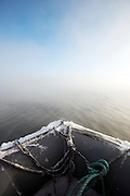 The bow of a Zodiac inflatable craft moves across misty waters of a lake at Jarfjord, near Kirkeness, Finnmark region, northern Norway