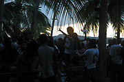 Partygoers dancing till sunrise at full moon beach party, Koh Som Island, Thailand.