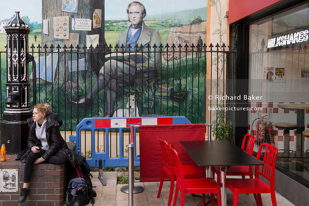 A young woman rests in front of a section of the Darwin mural located in front of a snack and milkshake bar in the pedestrianised area of Bromley town centre, on 3rd February 2020, in Bromley, London, England. Victorian evolutionist Charles Darwin lived in nearby Downe in Kent and his mural dates from 2009.