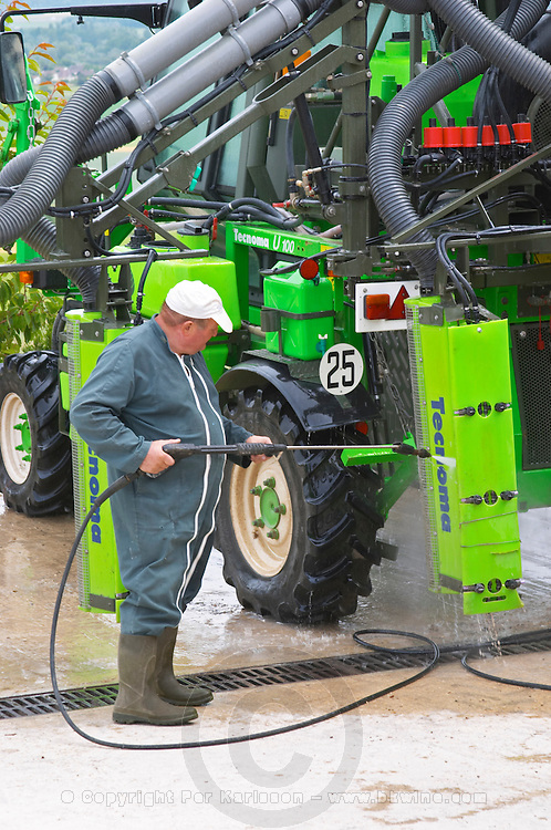 A man cleaning a vineyard tractor used for spraying at the experimental vineyard of the CIVC at Plumecoq near Chouilly in the Cote des Blancs It is used for testing clones soil treatment vine treatments spraying, Champagne, Marne, Ardennes, France