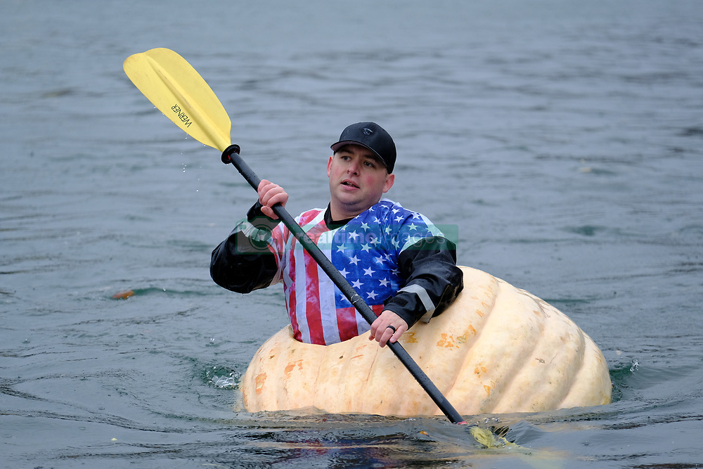 A police officer races a giant pumpkin across Lake of the Commons at the 14th annual West Coast Giant Pumpkin Regatta in Tualatin, Ore. on October 21, 2017. (Photo by Alex Milan Tracy)