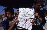 Traumatized kosovar Romany children Refugees with paintings in refugee camp<br /><br />Kosovar Roma Gypsy refugees who came to Italy via Mafia boats from Montenegro after the Kosovo war in 1999. Others lived in the no-mans land during the Bosnia war. They lived for years in UNHCR refugee camps. They are living with racism, prejudice and displacement from their homes. Many came to Italy from the Balkans in search of a new life after the violent disintegration of ex-yugoslavia. Since then they have been forced from their urban camps to live in Container camps outside cities. Brindisi and Bari, southern Italy 1999