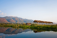 Burma/Myanmar, Inle Lake. Reflection of the Shan Hills and stilt houses in one of the Intha villages.