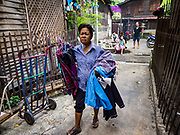 16 MAY 2017 - BANGKOK, THAILAND: A woman brings her laundry from a clothes line in Pom Mahakan. The final evictions of the remaining families in Pom Mahakan, a slum community in a 19th century fort in Bangkok, have started. City officials are moving the residents out of the fort. NGOs and historic preservation organizations protested the city's action but city officials did not relent and started evicting the remaining families in early March.           PHOTO BY JACK KURTZ
