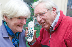 Older couple sharing the phone to listen into a conversation,