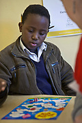 A young African boy throws a dice as part of playing a game called 'Cloud Sky' which he is playing with a volunteer reading coach in Zonnebloem School, Cape Town, South Africa.  The volunteer has been provided to the school by Shine Centre which is a charity that aims to address the high illiteracy rate in South Africa by improving literacy levels among children in schools and disadvantaged communities.
