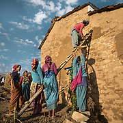 Women working on repairing a house. In the Himalaya.