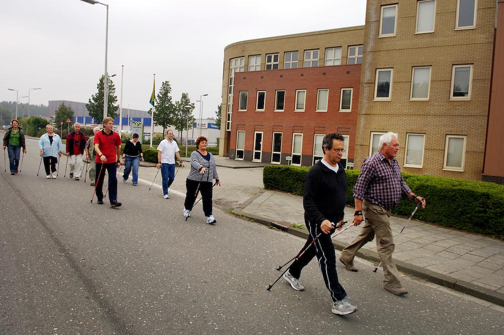 Nederland,  Rotterdam, 14 okt 2006<br /> Cursus nordic walking op een bedrijventerrein. Op zaterdag is het lekker rustig op het bedrijventerrein, kunnen mensen met overgewicht rustig hun looplessen volgen. Met nordic walking verstook je veel calorieen, daarom is het populair aan het worden in nederland. Er wordt ook veel uitgelachen over het lopen met stokken in ons vlakke landje. Het is een sportieve manier om van je overtollige kilo's af te vallen. De man in het rode shirt is de sportleraar, instructeur<br /> <br /> <br /> Foto: (c) Michiel Wijnbergh
