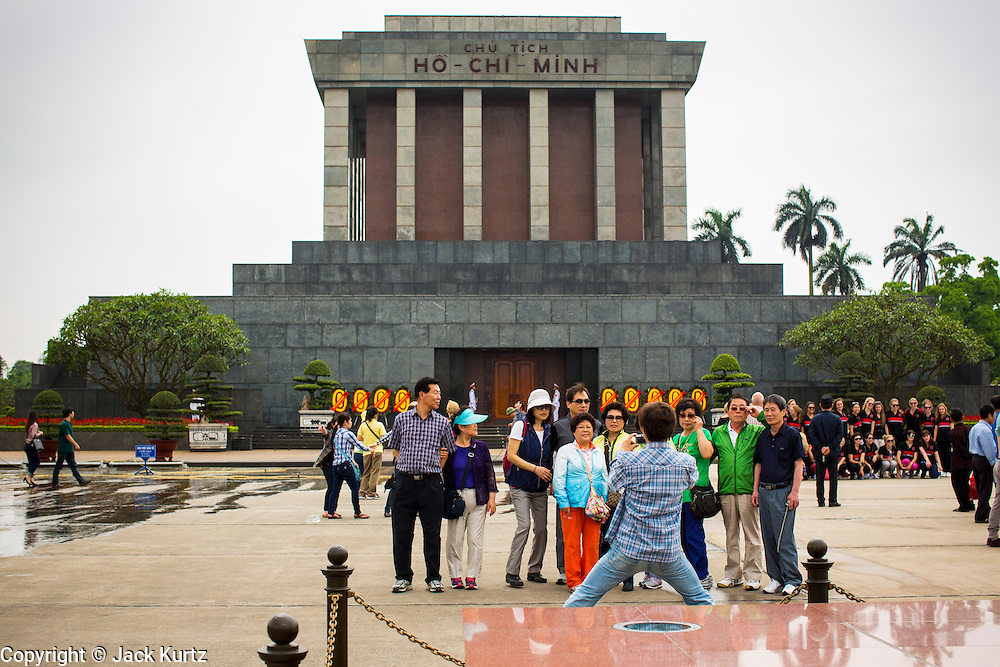 08 APRIL 2012 - HANOI, VIETNAM:    Tourists are photographed in front Ho Chi Minh's Mausoleum in Hanoi. The Ho Chi Minh Mausoleum, in Vietnamese: Lng Ch tch H Chí Minh, is a large memorial in Hanoi, Vietnam dedicated to Ho Chi Minh, the late leader of North Vietnam. It is located in the centre of Ba Dinh Square, which is the place where Ho read the Declaration of Independence on September 2, 1945, establishing the Democratic Republic of Vietnam. The mausoleum is 21.6 metres high and 41.2 metres wide.     PHOTO BY JACK KURTZ