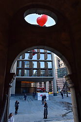 """© Licensed to London News Pictures. 15/02/2018. LONDON, UK.  London, UK.  15 February 2018.  A giant chubby heart balloon is seen outside Bloomberg's HQ in Queen Victoria Street during """"Chubby Hearts Over London"""", a design project conceived by Anya Hindmarch.  Supported by the Mayor of London, the British Fashion Council and the City of Westminster giant chubby heart balloons will be suspended over (and sometimes squashed within) London landmarks as a declaration of love to the city starting on Valentine's Day and continuing throughout London Fashion Week.  Photo credit: Stephen Chung/LNP"""