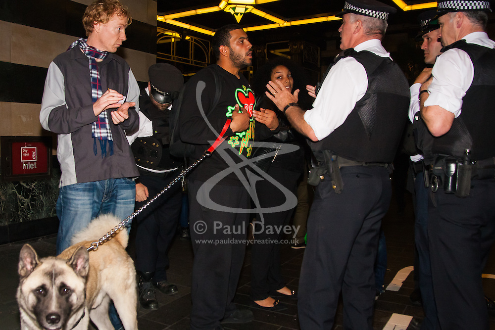 London, October 25th 2014. Dozens of Britain's Kurdish community and their supporters demonstrated outside the exclusive Savoy as Turkey's ambassador welcomed guests to a ball. The Kurds accuse Turkey of helping Jihadists from ISIS in eradicating Kurds, who have held a long campaign for an autonomous Kurdish state. Pictured: Police officers try to persuade a protester to leave the Savoy's forecourt.