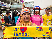 """14 JULY 2013 - BANGKOK, THAILAND:  About 150 members of the so called """"White Mask"""" movement marched through the central shopping district of Bangkok Sunday to call for the resignation of Yingluck Shinawatra, the Prime Minister of Thailand. The White Mask protesters are strong supporters of the Thai monarchy. They claim that Yingluck is acting as a puppet for her brother, former Prime Minister Thaksin Shinawatra, who was deposed by a military coup in 2006 and now lives in exile in Dubai.       PHOTO BY JACK KURTZ"""
