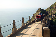 Man driving tractor across La Coupee narrow track between Sark and Little Sark, Island of Sark, Channel Islands, Great Britain