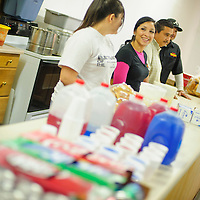 122212  Adron Gardner<br /> <br /> Lizet Garza, second from left, enjoys conversation with Kaylay Jaure at the serving counter as Badlands Burgers hosted a Feed the Needy holiday meal At Potter's House in Grants Saturday.