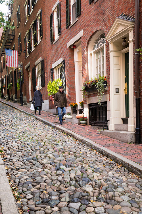 People walking in the famous cobbled street Beacon Hill in the historic district of Boston, Massachusetts at night, USA