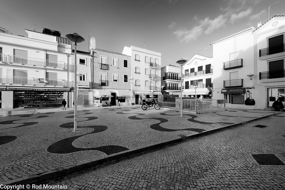 Nazaré, Portugal - February 12, 2018 - Nazaré Side Street 09 - Early morning light is beginning to illuminate the shops and restaurants in a small square in Nazare. <br /> <br /> Image: © Rod Mountain<br /> <br /> http://www.rodmountain.com<br /> http://bit.ly/Nazaré_bw<br /> http://bit.ly/Nazare_Portugal<br /> <br /> Nikon / Nikkor Lens<br /> @nikoncanada #NikonCA<br /> @NikonUSA #NikonNoFilter<br /> @nikoneurope #NikonEurope<br />  <br /> @visitportugal <br /> <br /> @municipiodanazare @cmnazare @CMNazareMata <br /> <br /> #turismoemportugal #turismo #rotaportugal <br /> #awesomebnw #traveldeeper #theworldshotz #TheGlobeWanderer #everydayportugal #CantSkipPortugal #travelblog#agameoftones #ourstreets #timeless_streets #monochrome #blackandwhitephotography #photographyislife #blacknwhitepic #foto_bw #bnw_captures #bwsquare #blackandwhiteonly #featuremeinstagood #travelblog #nikonshooters #lovetotravel <br /> <br /> https://www.visitportugal.com/en<br /> https://en.wikipedia.org/wiki/Portugal<br /> https://en.wikipedia.org/wiki/Nazaré,_Portugal<br /> http://www.cm-nazare.pt/en