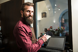 Portrait of restaurant owner writing in note pad while standing by computer